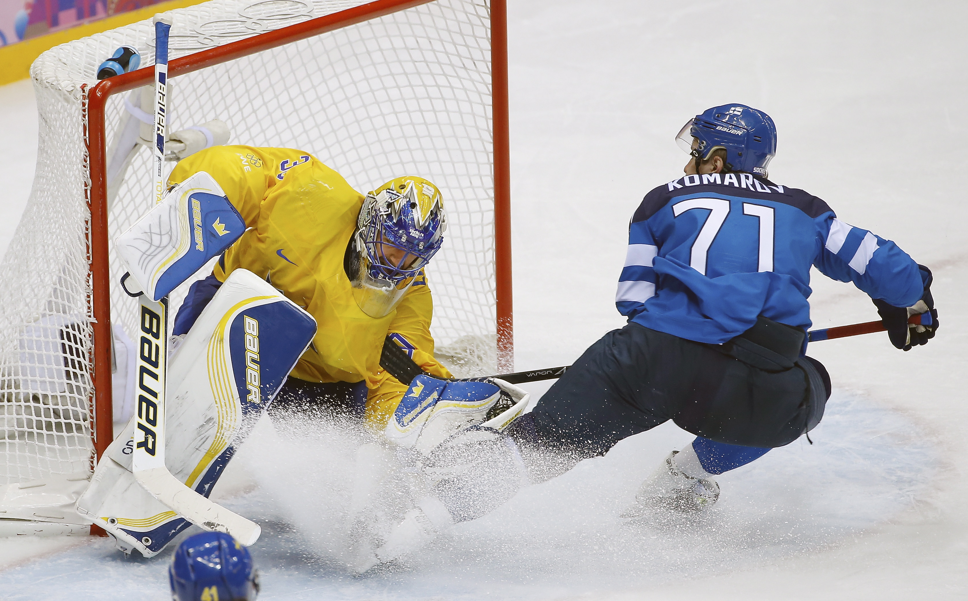 Finland forward Leo Komarov skates into Sweden goaltender Henrik Lundqvist during the third period of the men's semifinal ice hockey game at the 2014 Winter Olympics, Friday, Feb. 21, 2014, in Sochi, Russia. (Matt Slocum/AP)