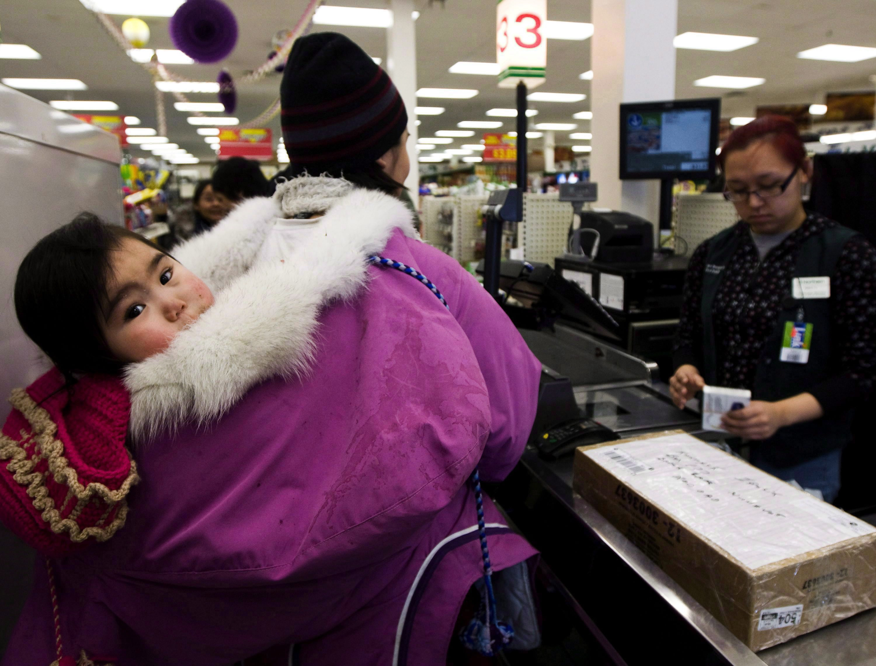 Pauline Kadjuk, 1, is carried in a Amautik by her mother Brittany Ikulik, middle, while paying for groceries at the Northern store in the small town of Baker Lake, Nunavut on March 25, 2009.