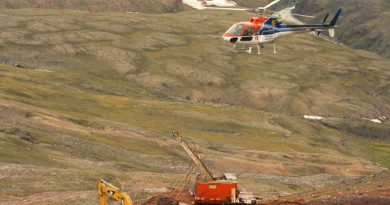A helicopter passes over excavation equipment at the Mary River exploration camp, the site of a proposed iron mine on northern Baffin Island, in 2006. (Vinnie Karetak/Canadian Press)