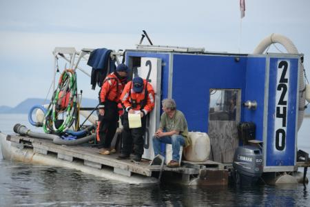 Coast Guard Sector Anchorage enforcement department personnel conduct a boarding aboard a gold dredge vessel near Nome, Alaska, Aug. 3, 2014. Boardings are conducted to ensure that vessel crews are operating safely and complying with environmental regulations. ( Petty Officer 2nd Class Grant DeVuyst / U.S. Coast Guard)