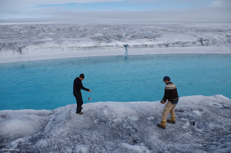 Throwing a level logger to measure temperature and pressure into a supraglacial river, Greenland. (Mia Bennett / August 2014)