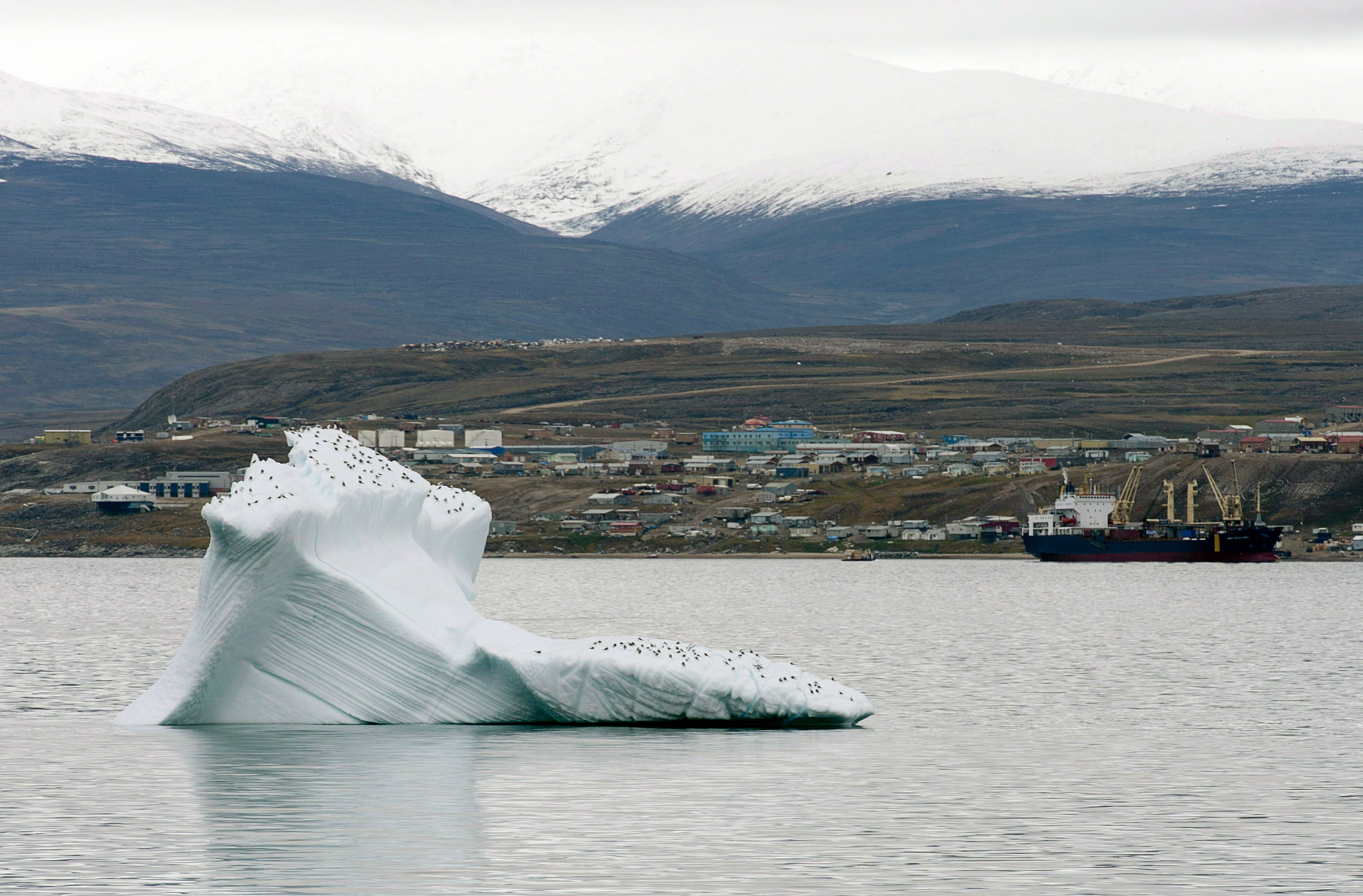 Ice floats past a cargo ship and the hamlet of Pond Inlet in Canada's eastern Arctic in August 24, 2014. (Adrian Wyld / The Canadian Press)