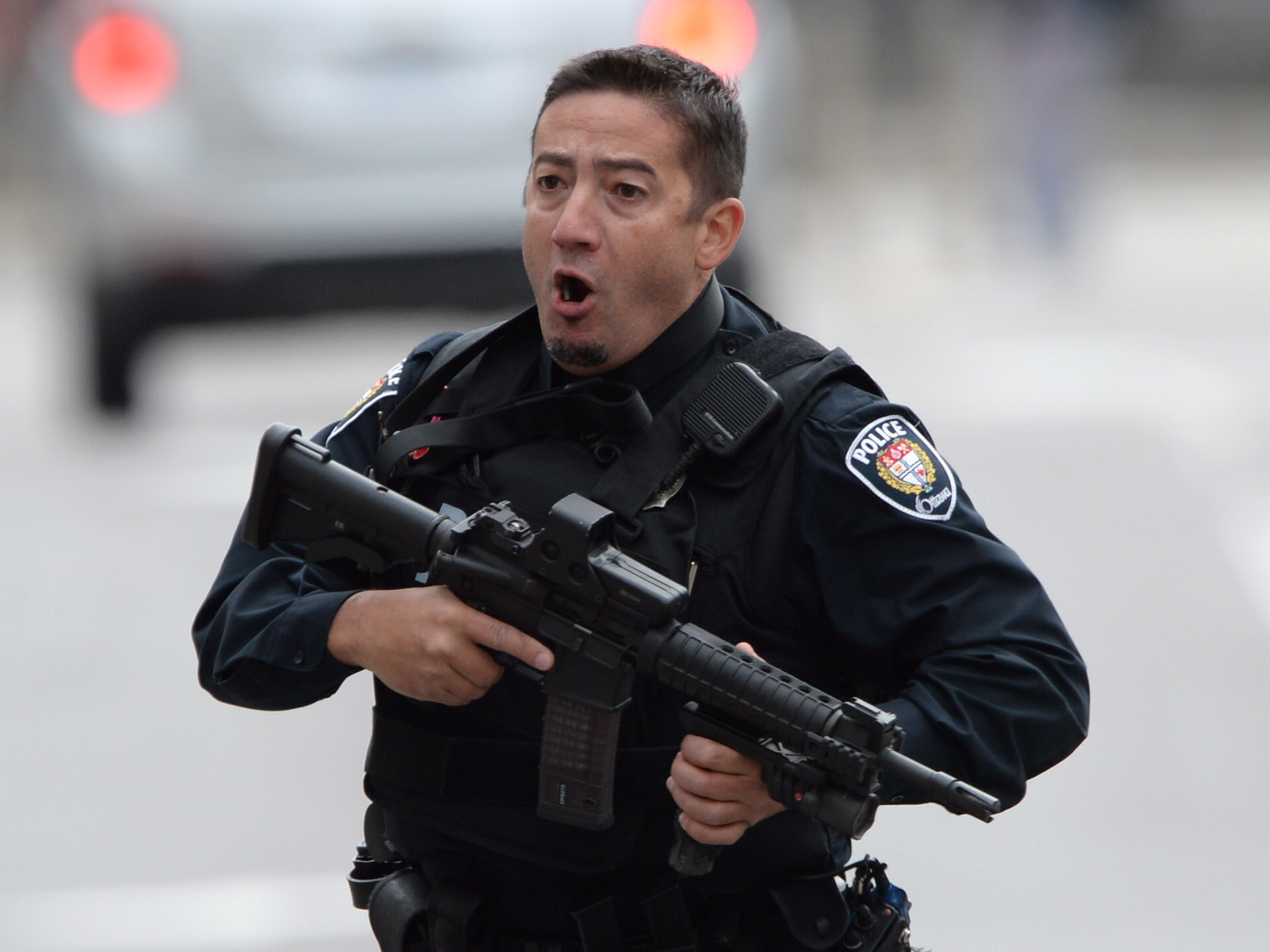 An Ottawa police officer runs with his weapon drawn in Ottawa on Wednesday Oct.22, 2014. (Sean Kilpatrick / The Canadian Press)