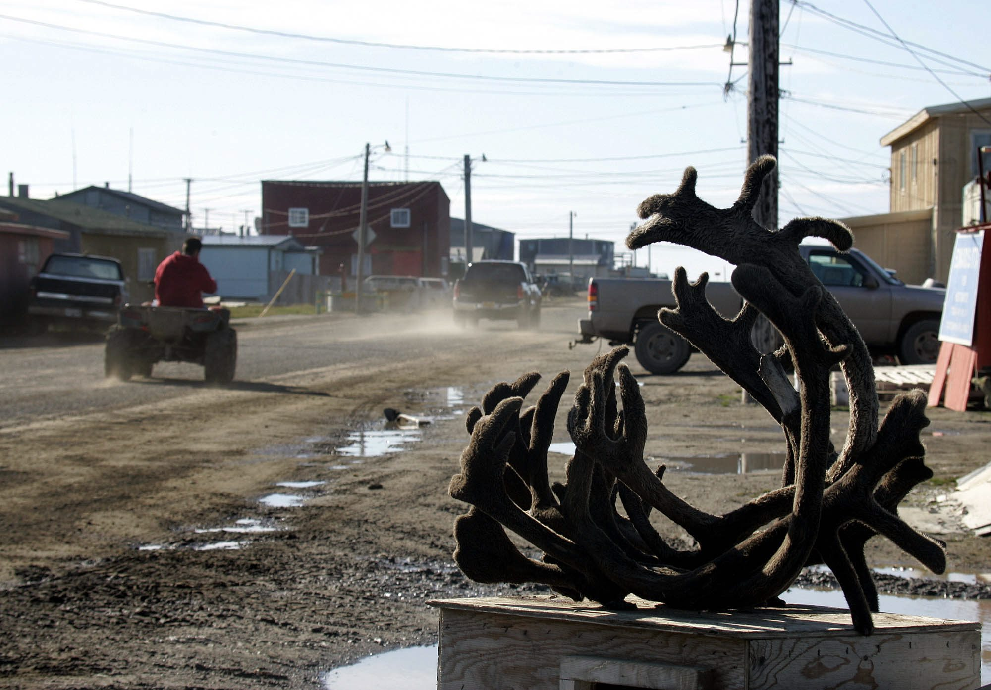 An ATV drives past caribou horns on one of the dirt roads in the Arctic town of Barrow, Alasksa. (Al Grillo / AP)