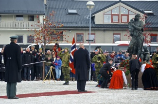 King Harald V of Norway pays his respects to a statue to the mothers and children of war in Kirkenes town square as part of the liberation ceremonies. (Emma Jarratt/Barents Observer)