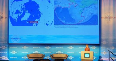 U.S. Senator Lisa Murkowski addresses Arctic Circle 2014 in Reykjavik, Iceland, with a map behind her of two polar opposite cities in the Arctic. (Mia Bennett)