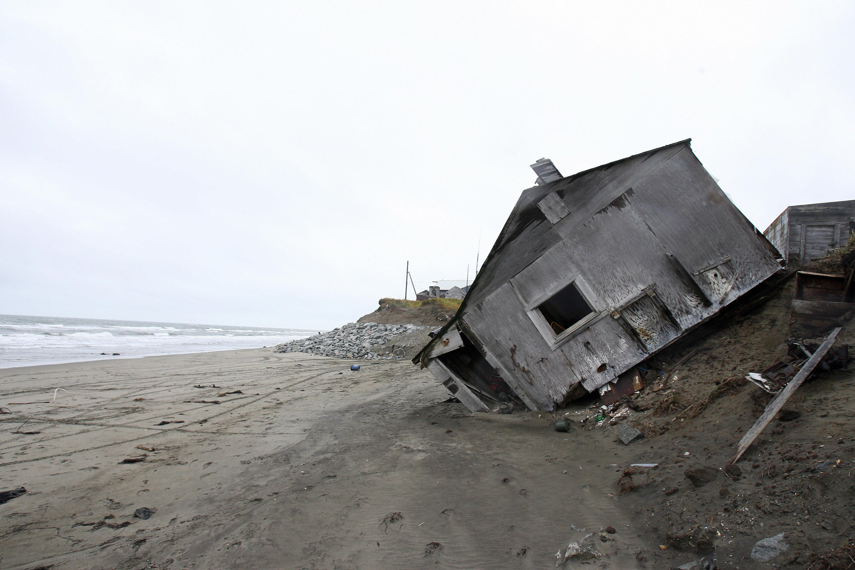A home in Shishmaref, Alaska in 2006. Temperatures that have risen 15F (4.4C) over the last 30 years are causing a reduction in sea ice, thawing of permafrost along the coast, making the shoreline vulnerable to erosion.  (Gabriel Bouys/AFP/Getty Images)