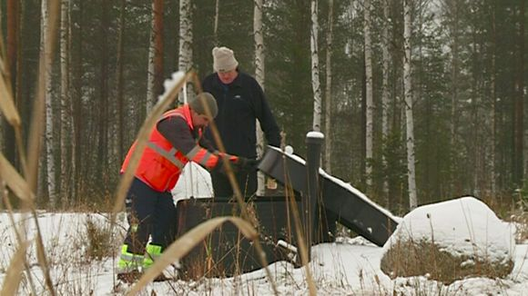 Saloy CEO Tapio Salminen (right) demonstrates the use of a phosphorus recovery device. (Yle)