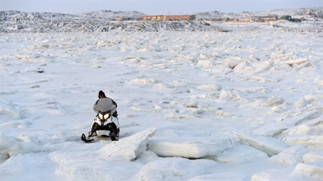 A snowmobiler makes his way through the ice on Frobisher Bay outside of Iqaluit. Canada's Arctic capital of 7,000, like other Arctic communities, is growing rapidly, in part due to migration from smaller communities, according to the second Arctic Human Development Report. (Sean Kilpatrick/Canadian Press)