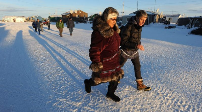 Millie Hawley and Interior Secretary Sally Jewell walk down the main street in the Inupiat village of Kivalina, Alaska on Monday, Feb. 16, 2015. The village is threatened by coastal erosion of the long barrier island between the Chukchi Sea and a lagoon at the mouth of the Kivalina River. (Bill Roth / Alaska Dispatch News)