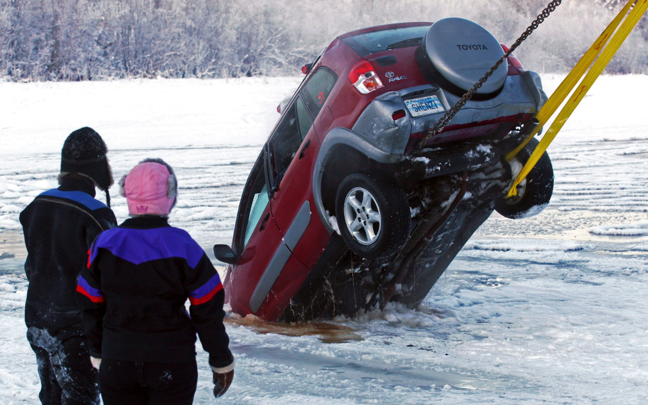 A dive crew watches the recovery of a vehicle from the icy water near the Pike's Landing Chena River Ice Bridge entrance in Fairbanks, Alaska on Dec. 19, 2014. (Eric Engman /The Fairbanks Daily News-Miner/AP)