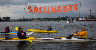 Kayaktivists Jordan Van Voast and Martin Adams hold a sign in protest of the arrival of Shell's Arctic drilling vessel the Noble Discoverer as it came into Everett, Wash. on Tuesday, May 12, 2015. (Daniella Beccaria/seattlepi.com via AP)