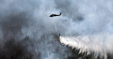 """A """"Bambi Bucket,"""" hanging from a helicopter releases hundreds of gallons of water onto the Stetson Creek Fire near Cooper Landing, Alaska on June 17, 2015. (Sgt. Balinda O'Neal/U.S. Army National Guard via AP)"""