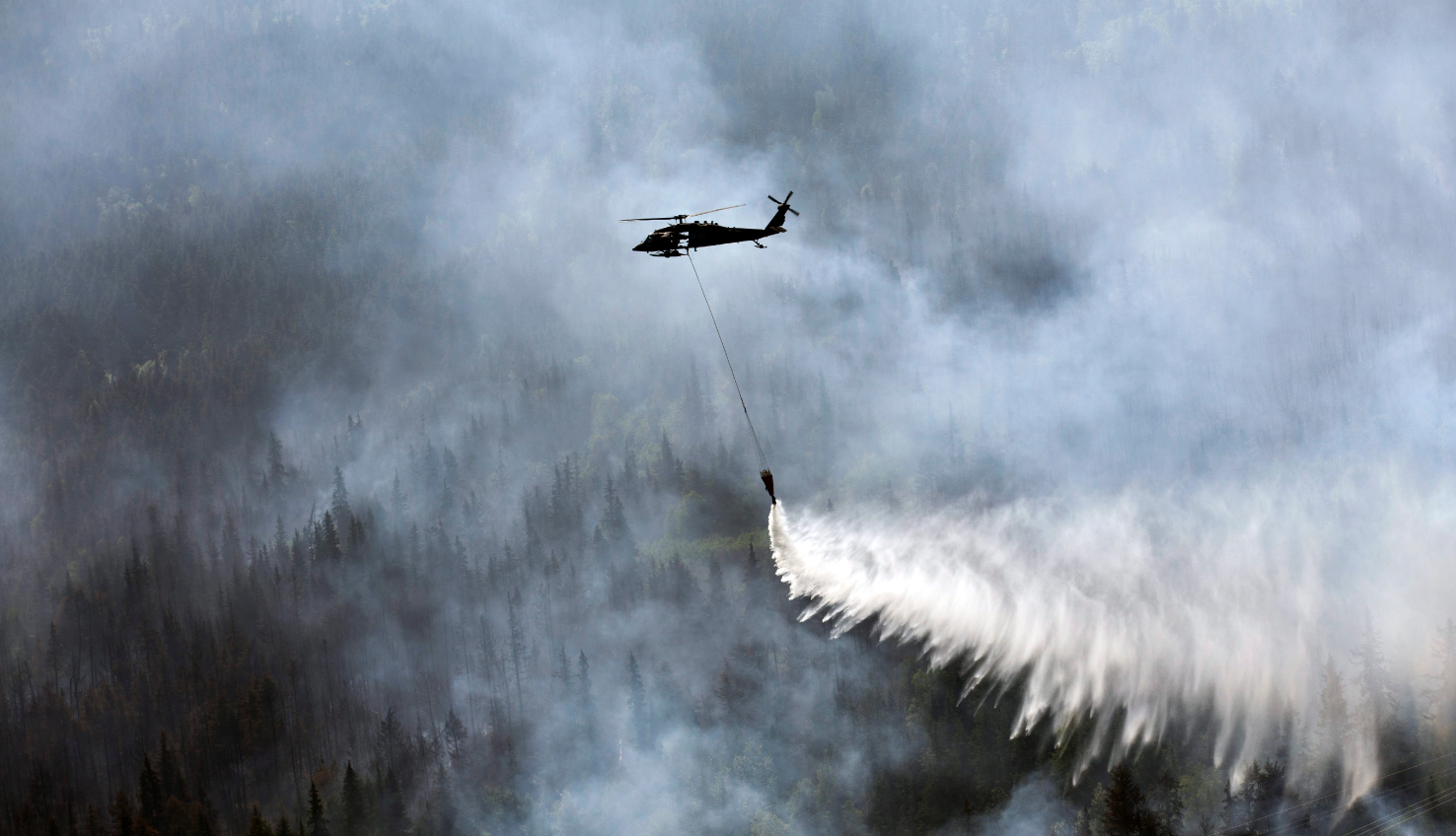 "A ""Bambi Bucket,"" hanging from a helicopter releases hundreds of gallons of water onto the Stetson Creek Fire near Cooper Landing, Alaska on June 17, 2015. (Sgt. Balinda O'Neal/U.S. Army National Guard via AP)"