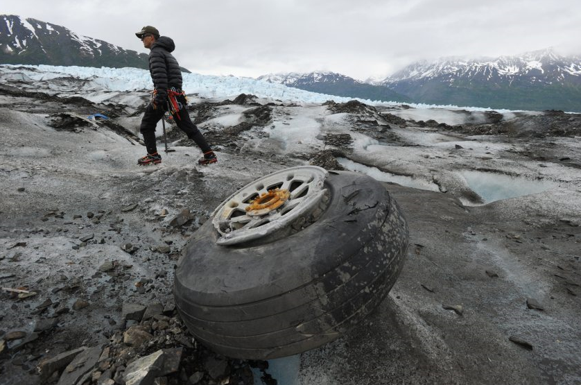 U.S. Marines Capt. David Gooch, with the Defense POW/MIA Accounting Agency, walks past an aircraft wheel assembly resting on the ice surface of Colony Glacier in Alaska on Wednesday, June 10, 2015. For the fourth consecutive summer, a team of military members and scientists are combing the surface of Colony Glacier looking for remains and personal effects that can be used to identify the 52 people who perished when a U.S. Air Force Douglas C-124 Globemaster II crashed into Mount Gannett, about 15 miles away, while flying in severe weather in 1952. (Bill Roth/Alaska Dispatch News)