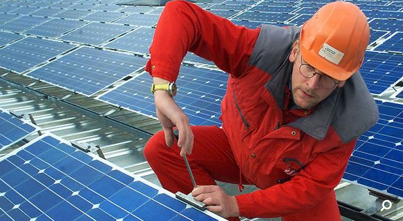 Worker installs solar panels. File photo. (Yle)
