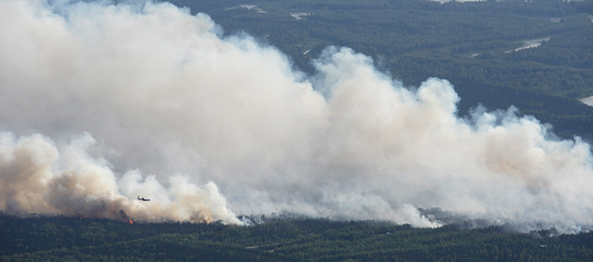 A State Division of Forestry air tanker works the Sockeye fire north of Kashwitna Lake on Sunday, June 14, 2015, near Willow, Alaska.  (Bill Roth / Alaska Dispatch News via AP)