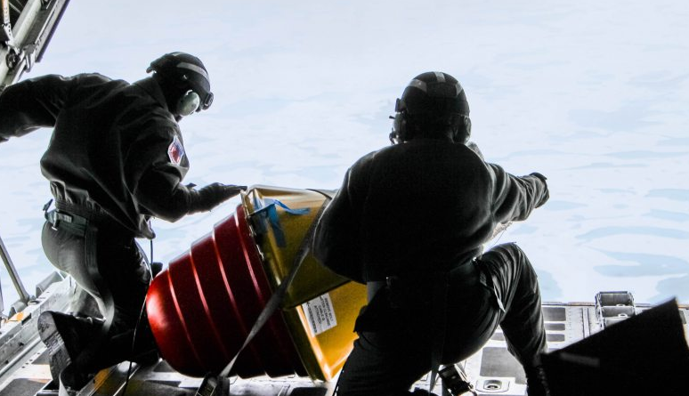Two U.S. Coast Guard drop masters on an Arctic Domain Awareness flight push a weather buoy into the ocean north of Deadhorse on Tuesday, July 14, 2015. (Kamala Kelkar/Alaska Dispatch News)