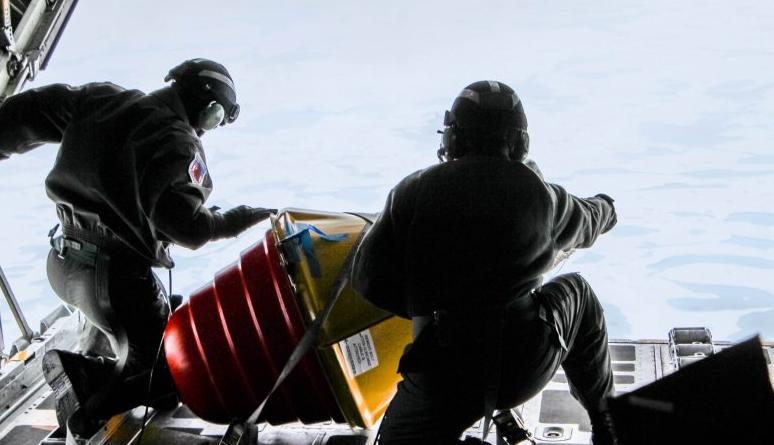 Two U.S. Coast Guard drop masters on an Arctic Domain Awareness flight push a weather buoy into the ocean north of Deadhorse on Tuesday, July 14, 2015. (Kamala Kelkar/Alaska Dispatch News)