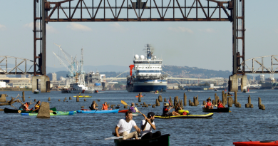 oaters gather as the Royal Dutch Shell PLC icebreaker Fennica heads under a railroad bridge and up the Willamette River in Portland, Ore., Thursday, July 30, 2015. The Fennica left dry dock and made its way down the Willamette River toward the Pacific Ocean soon after authorities forced the demonstrators from the river and the St. Johns Bridge. (Don Ryan/AP)