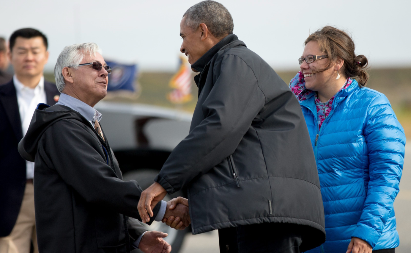 U.S. President Barack Obama is greeted by Mayor Maija Lukin, right, and Northwest Arctic Borough Mayor Reggie Joule, left, as he arrives at Ralph Wien Memorial Airport, Wednesday, Sept. 2, 2015, in Kotzebue, Alaska. Many experts see Obama's visit as important foreshadowing for the UN climate summit in Paris later this year.(Andrew Harnik/ AP)