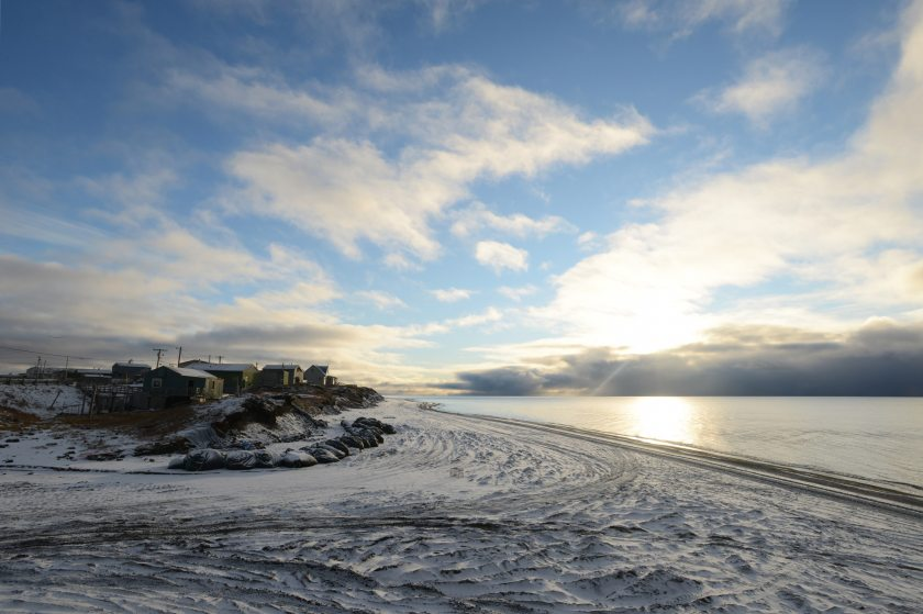 Following a snowstorm, the sun makes an evening appearance in the bluffs that include the Ukkuqsi archaeological site in Barrow, Alaska. Sand bags help protect the site, which once again yielded human remains following a late-August storm. (Erik Hill/Alaska Dispatch News)