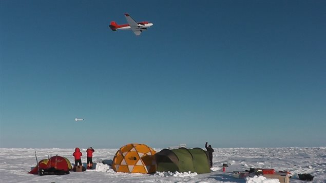 A research plane tows an electromagnetic sonsor (seen in the sky just above the two researchers in red) The equipment gives a far more reliable reading of ice thickness than can be ascertained from satellite readings. (Courtesy ChristianHaas)