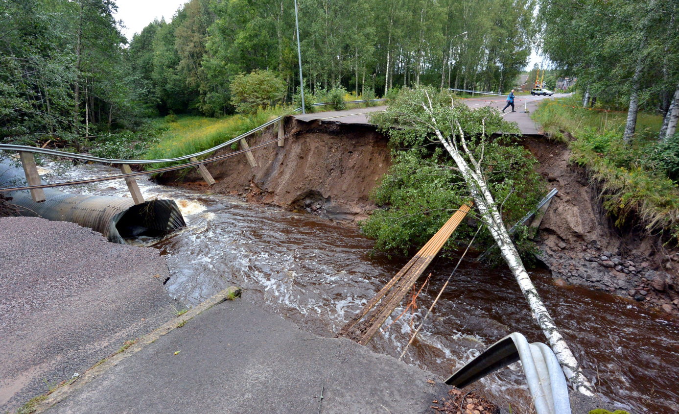 A rain-swollen river has washed away the road and felled trees in Kristinehamn, western Sweden, on August 22, 2014. Emergency workers at the time said floods had reached catastrophic levels after heavy rains. (Johan Nilsson/AFP/Getty Images)