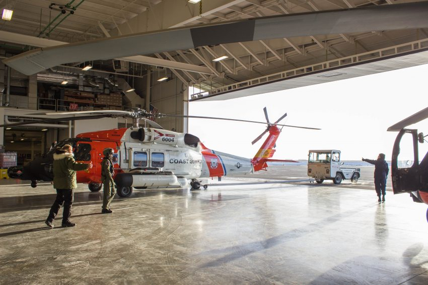 The Coast Guard crew at a forward operating location in Deadhorse direct a Jayhawk helicopter out of its hander and onto the tarmac on October 11, 2015. The departure of the Coast Guard was delayed by a day due to a valve malfunction. (Asaf Shalev/Alaska Dispatch News)
