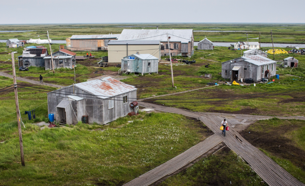 People walk down the elevated, raised wooden sidewalks - created so people don't sink into the melting permafrost - on July 5, 2015 in Newtok, Alaska. The community's generator broke this week forcing residents to burn wood and cardboard to heat their homes. (Andrew Burton/Getty Images)