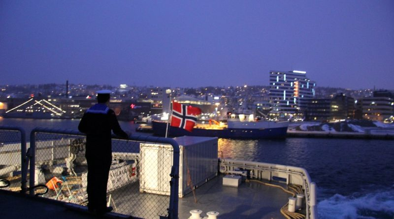 A sailor looks out at Tromso, Norway from the Norwegian icebreaker KV Svalbard. (Eilis Quinn/Eye on the Arctic)