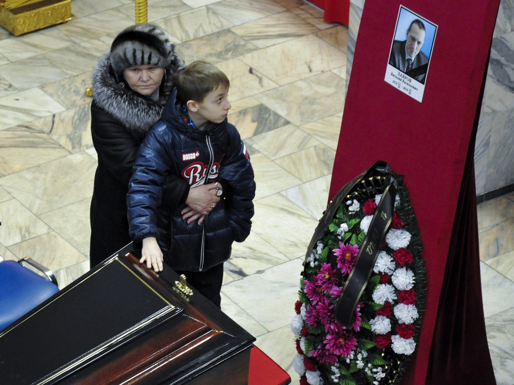 Relatives stand next to the coffin of Vitaly Lavrov, one of the dead miners, during a funeral in Vorkuta, a town north of the Arctic Circle in Russia Monday, Feb. 29, 2016. (Semen Volodin/AP Photo)