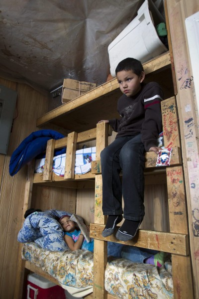 Seven-year-old Ferlin Lahtal (right) and his sister, five-year-old Verna sit in their home-made bunk beds in thier home in Attawapiskat, Ontario Saturday December 17, 2011. Twenty-one people live in the house that has plastic on the ceilings to stop water entry. FRANK GUNN/THE CANADIAN PRESS
