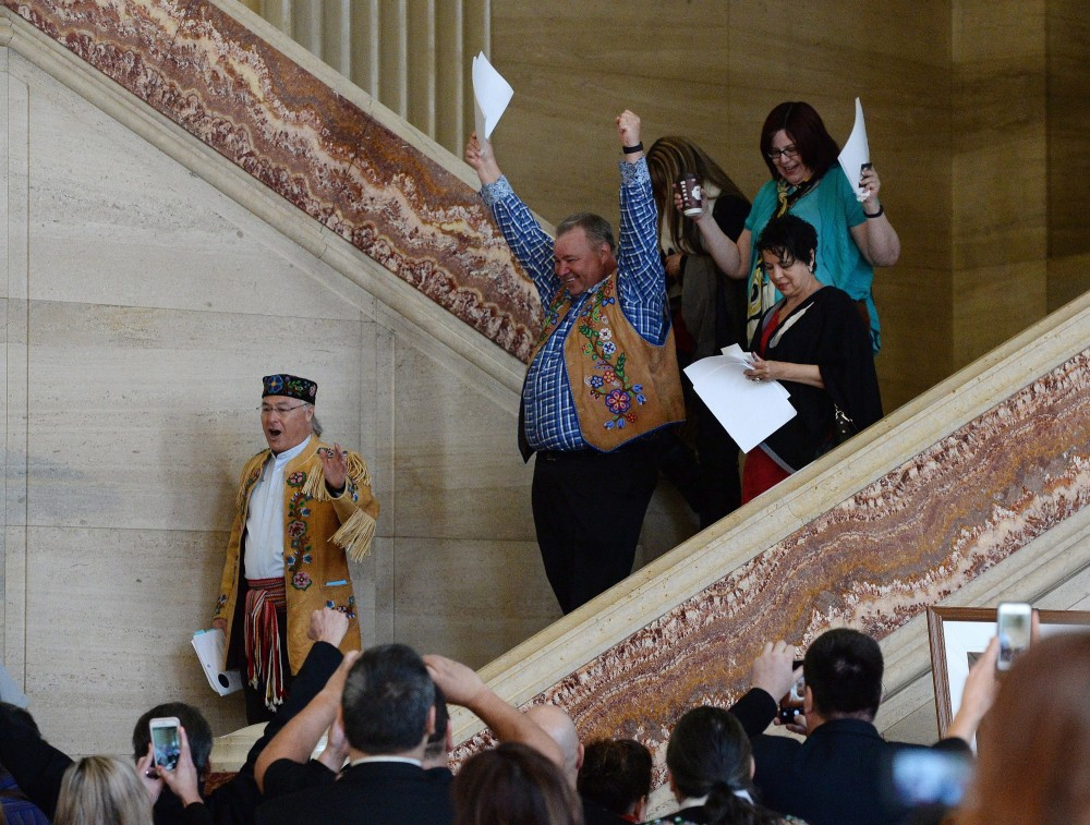 Metis National Council President Clement Chartier, left, and David Chartrand, president of the Manitoba Metis Federation, centre, celebrate following the decision at the Supreme Court of Canada in Ottawa on Thursday, April 14, 2016. Sean Kilpatrick/THE CANADIAN PRESS