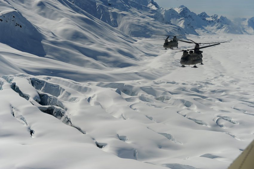 Two Chinook Helicopters pass over a crevasse field as Fort Wainwright soldiers haul tents, fuel and food up to the Kahiltna Glacier for the National Park Service Denali mountaineering camp on Sunday, April 24, 2016. Bob Hallinen / ADN