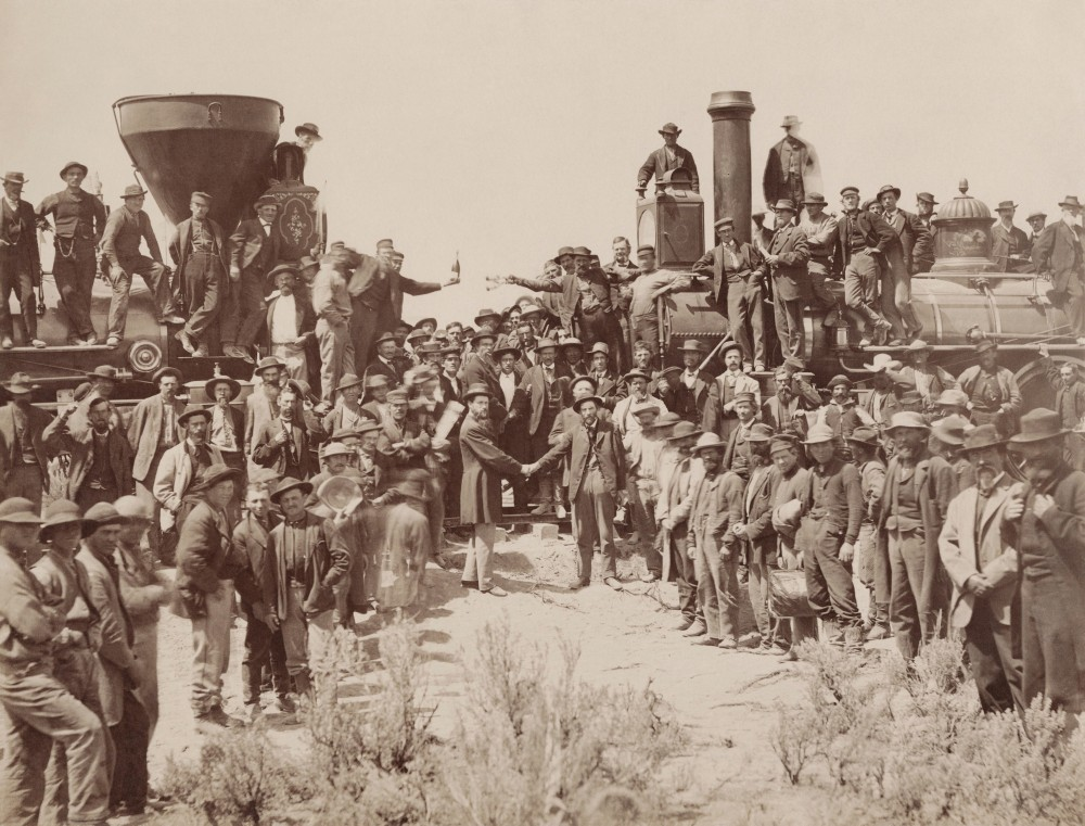 "A.J. Russell image of the celebration following the driving of the ""Last Spike"" at Promontory Summit, U.T., May 10, 1869. By Andrew J. Russell - Yale University Libraries, Public Domain, https://commons.wikimedia.org/w/index.php?curid=41243910"