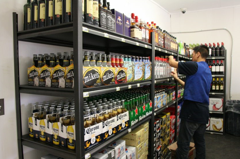 An Alaska Commercial Co. worker stocks the shelves of the AC liquor store in Bethel, Alaska, on opening day, Tuesday, May 3, 2016. The new liquor store offers the first legal sales of alcohol in Bethel in more than 40 years. (Lisa Demer/Alaska Dispatch News)