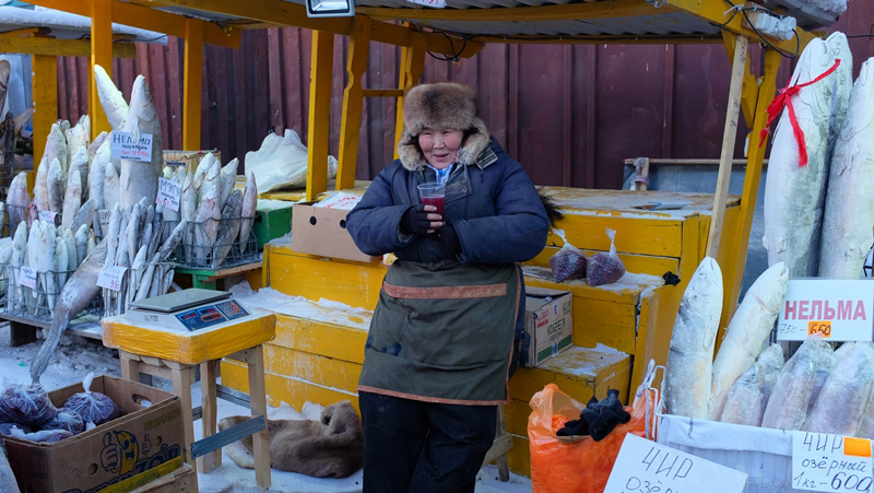 A fish vendor drinking berry juice at the local market in Yakutsk. Life is pretty good!