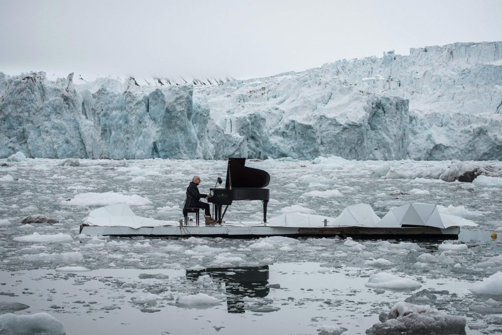 In this undated photo provided by Greenpeace Spain, Italian composer and pianist Ludovico Einaudi performs one of his own compositions on a floating platform in the Arctic Ocean, in front of the Wahlenbergbreen glacier, in Svalbard, Norway. (Pedro Armestre/Greenpeace Spain via AP)