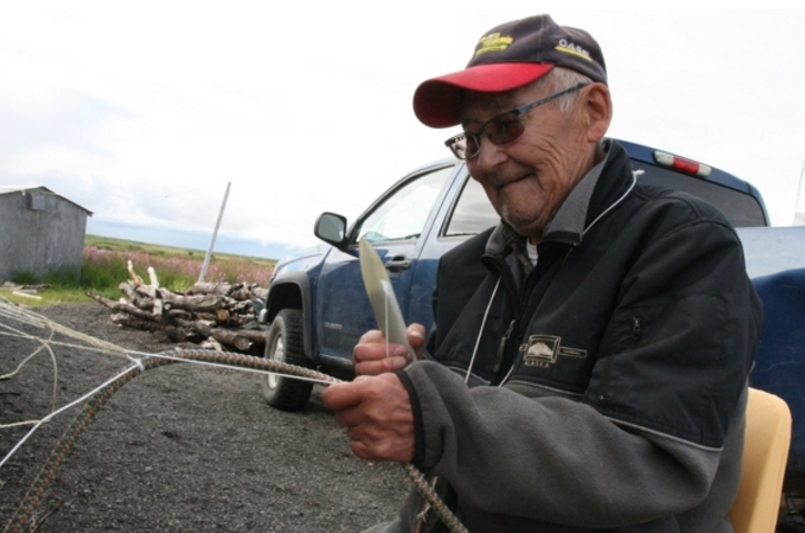 Quinhagak fisherman Jimmy Anaver on Friday, July 22, 2016, shows how he hangs floats onto his net. (Lisa Demer / Alaska Dispatch News)