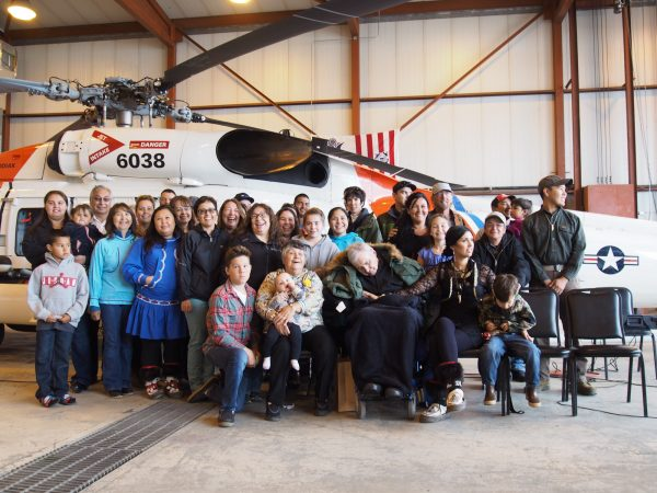 Members of the Schaeffer family pose for a picture after the dedication ceremony. Mary Schaeffer sits in the front row, next to John, pictured wearing a green jacket. (Zachariah Hughes/ Alaska Public Media – Kotzebue)