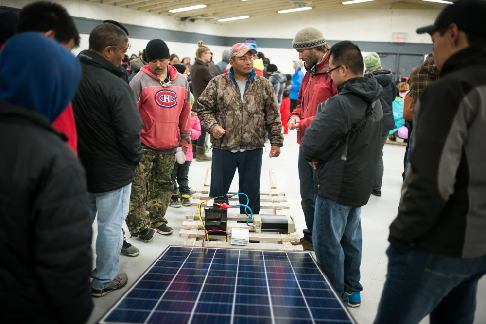 Lootle Arreak (in red) and Esa Quillaq (in camouflage) speak with Vancouver Renewable Energy Coop Solar Installer, Duncan Martin about solar panels, at Clyde River community centre. (Greenpeace)