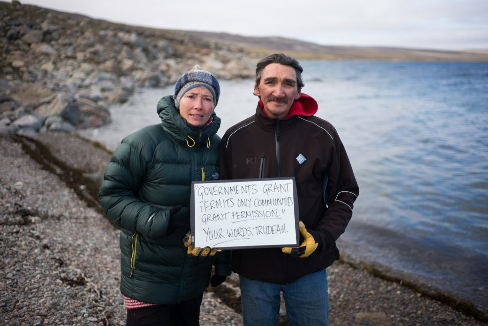 Actor, writer and activist, Emma Thompson and former mayor of Clyde River, Jerry Natanine hold a sign near Clyde River. (Greenpeace)