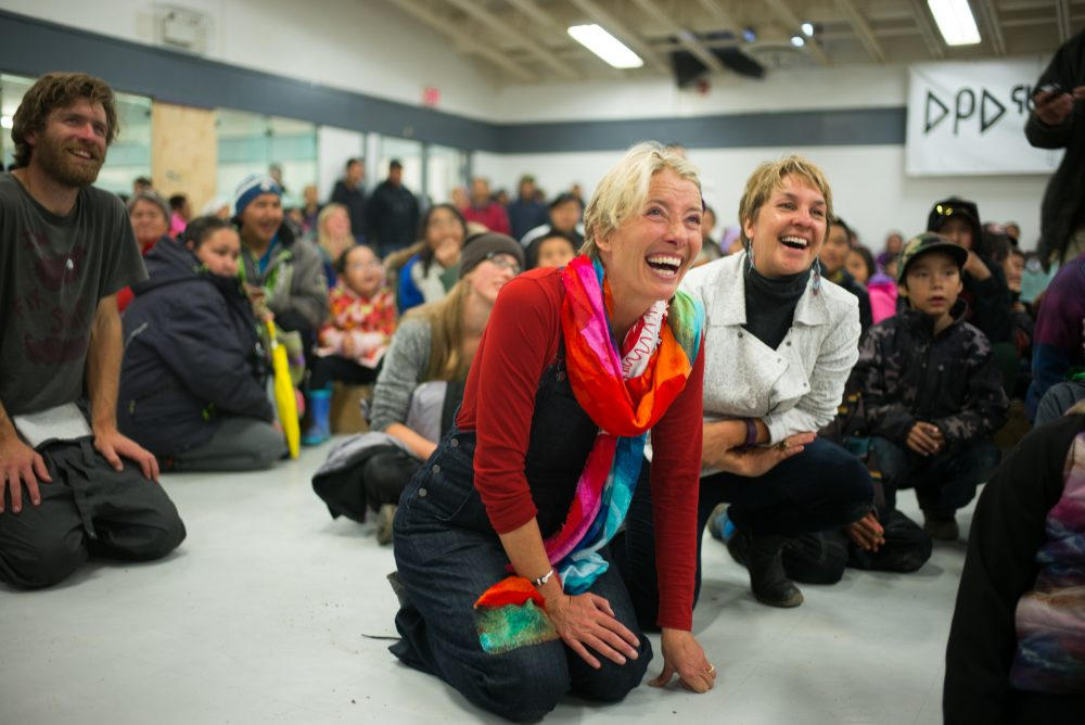 Vancouver Renewable Energy Coop Solar Installer, Duncan Martin (L), actor, writer and activist, Emma Thompson and Executive Director of Greenpeace Canada, Joanna Kerr watch entertainment during the solar celebration at the Clyde River community centre.