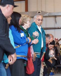 Around 200 people attended the dedication ceremony, including Willie Hensley, pictured here in the green atikłuk. (Zachariah Hughes/ Alaska Public Media – Kotzebue)