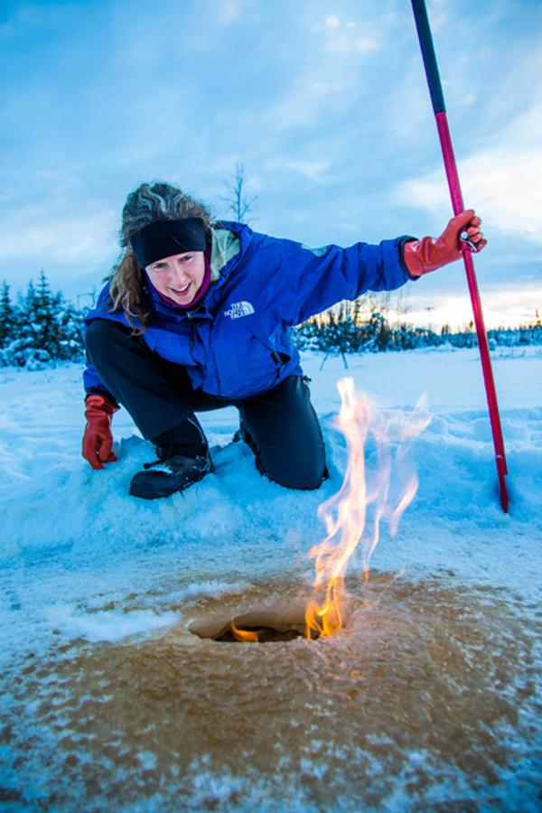 Research associate professor Katey Walter Anthony inspects flaming methane gas seeping from a hole in the ice on the surface of a pond on the UAF campus. The naturally occurring phenomenon is made worse by thawing permafrost and increased plant decay caused by global warming. (Todd Paris / UAF)