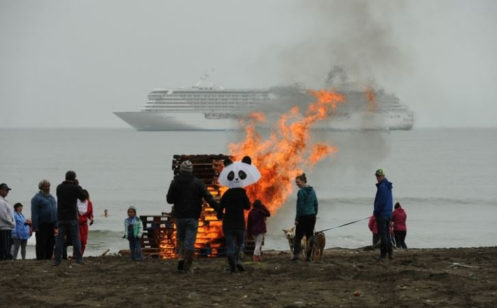 A bonfire blazes on the beach as the Crystal Serenity cruise ship lies at anchor in Nome on Sunday, Aug. 21, 2016. The bonfire was part of a polar swim in the Bering Sea. Locals swam in the cold water as a few ship passengers watched from shore. (Bob Hallinen / Alaska Dispatch News)