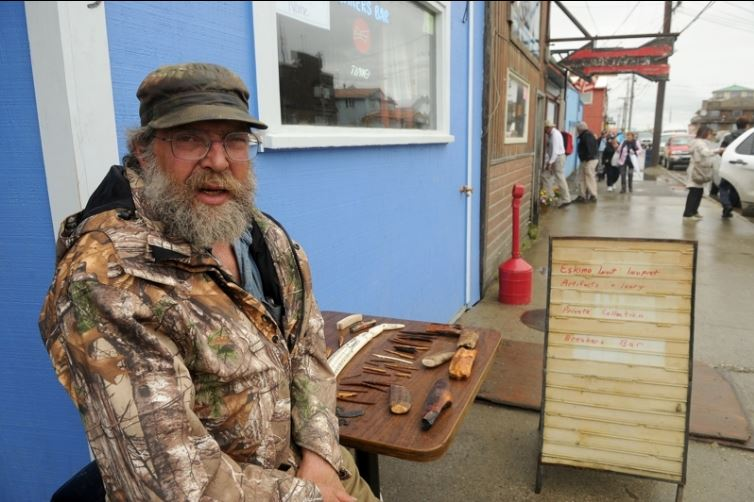 Roger Thompson offers ivory for sale to passengers of the Crystal Serenity cruise ship in Nome, AK in front of the Breakers Bar on Sunday, August 21, 2016. The cruise ship is on its way across the Northwest Passage, the largest passenger ship to attempt the crossing. (Bob Hallinen / Alaska Dispatch News)