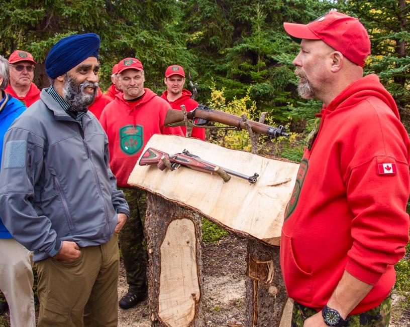 Member of the Canadian Rangers explains the differences between the current Lee Enfield model (top) and the new rifle (bottom) to Minister Sajjan (L) during his visit to Operation NANOOK. (Canadian Armed Forces)