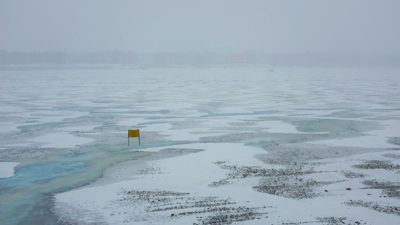 The frozen Amur river separating Russia and China between the cities of Blagoveshchensk and Heihe. The yellow sign in the frozen river warns onlookers not to cross. (Mia Bennett)